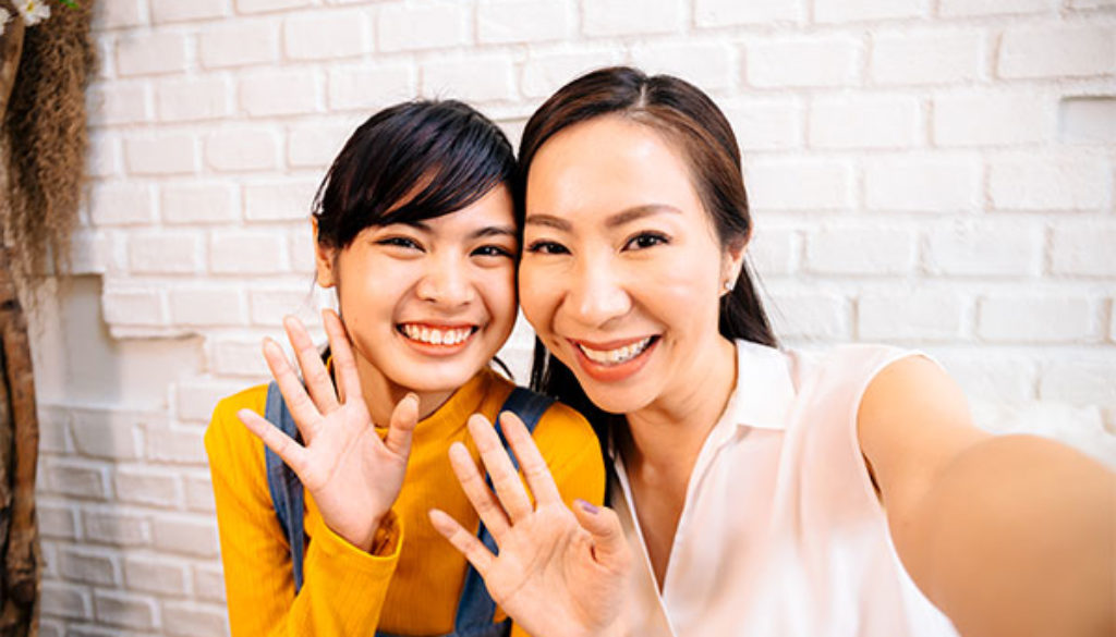 Face of smiling happy Asian teenage daughter and Asian middle-aged mother